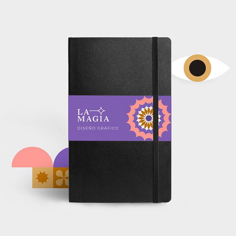 """Una agenda con el logotipo de La Magia y elementos ilustrados abstractos alrededor (formas geométricas y un ojo). Portada del artículo """"cómo organizar tu tiempo en el trabajo"""""""